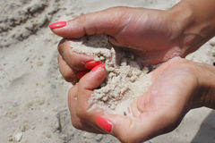 Female hands hold the sand close-up. Stock Images
