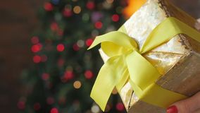 Female hands hold and show the gift. Close up Gift, female hands hold and show the gift, the golden box is bandaged with yellow tape. Bright festive background stock video footage