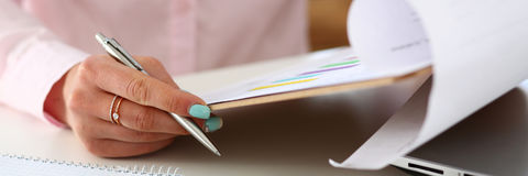 Female hands hold silver pen and pad Stock Photography