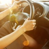 Female hands hold the steering wheel, close-up. A woman is driving a car. Selective focus. Toned. Square photo stock image
