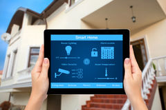 Female hands hold a tablet with system smart house on the background of the house