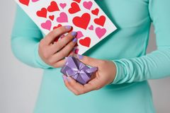 Female hands hold a valentine in the form of a paper heart. Valentine`s Day stock image