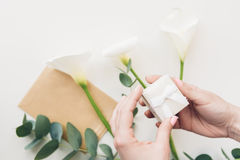 Female hands hold white gift box on background of flowers and phone. top view Stock Images