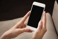 Female hands hold white phone in their hands. Mobile phone close-up.  stock photo