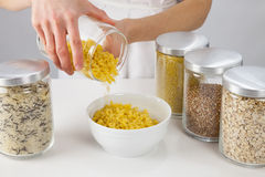Female Hands Holding A Pot With Raw Macaroni Stock Photo