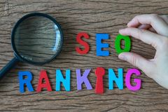 Female hands holding alphabet O on colorful wooden SEO RANKING a. Nd magnifying glass as SEO Search engine optimisation concept Stock Image