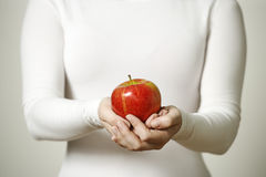 Female hands holding apple. Image of a female holding a ripe red apple Royalty Free Stock Photo