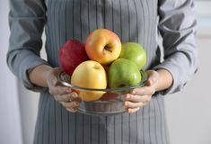Female hands holding apples in bowl, Royalty Free Stock Photography