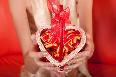 Female hands holding basket in shape of heart Stock Images