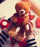 Female hands holding bear with a heart. Female hands holding brown fluffy bear with a heart stock image