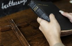 Female hands holding a bible and a wooden cross stock photo