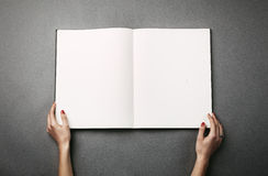 Female hands holding a big open book. Horizontal Royalty Free Stock Photography
