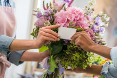 Female hands holding blank business card and bouquet of beautiful flowers. Close-up partial view of female hands holding blank business card and bouquet of Stock Photography
