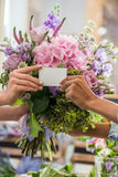 Female hands holding blank business card and bouquet of beautiful flowers. Close-up partial view of female hands holding blank business card and bouquet of Royalty Free Stock Photography