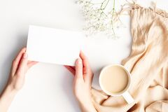 Free Female Hands Holding Blank Paper Card Over Cozy Home White Desk With Cup Of Coffee, Blanket, Flowers. Hygge, Autumn Fall, Comfort Stock Photo - 179525510