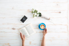 Female hands holding book and coffee cup on wooden desk. Female hands holding open book and coffee cup on the wooden desk stock image