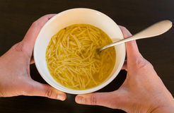 Female hands holding a bowl with European noodle soup. Female hands holding a white bowl full of European noodle soup with spoon on a brown wooden table Stock Photography
