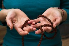 Female hands holding buddhist mala rosary with rudraksha beads. Female hand holding a buddhist mala rosary with rudraksha beads, wearing green shirt stock photography