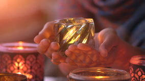 Female hands holding a candle in the transparent glass shining in the darkness as a symbol of celebration, meditation. Hands holding a candle in the transparent stock footage