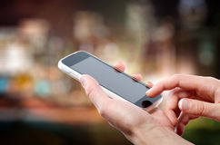Female hands holding a cell phone (smartphone) with tuchscreen in night Royalty Free Stock Images