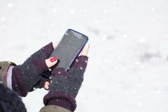 Female hands holding a cellphone outdoors in the snow Royalty Free Stock Photography