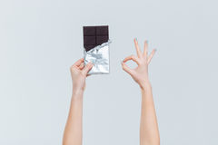 Female hands holding chocolate and showing ok sign Stock Photography