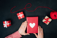 Female hands are holding a christmas gift on black. Background Stock Photos