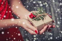 Female hands holding Christmas gift box with branch of fir tree, shiny xmas background. Royalty Free Stock Images