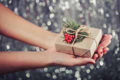 Female hands holding Christmas gift box with branch of fir tree, shiny xmas background. Royalty Free Stock Image