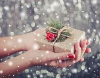 Female hands holding Christmas gift box with branch of fir tree, shiny xmas background. Stock Images