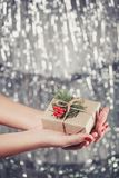 Female hands holding Christmas gift box with branch of fir tree, shiny xmas background. Holiday gift and decoration. Toning Royalty Free Stock Photos