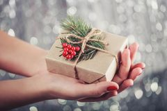Female hands holding Christmas gift box with branch of fir tree, shiny xmas background. Holiday gift and decoration. Toning Royalty Free Stock Image