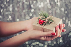 Female hands holding Christmas gift box with branch of fir tree, shiny xmas background. Holiday gift and decoration Royalty Free Stock Image