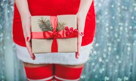 Female hands holding Christmas gift box with red ribbon, branch of fir tree on shiny xmas background. Holiday gift and decoration. Royalty Free Stock Image