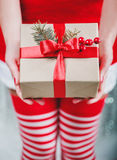 Female hands holding Christmas gift box with red ribbon, branch Royalty Free Stock Images