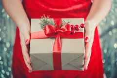 Female hands holding Christmas gift box with red ribbon, branch of fir tree on shiny xmas background. Holiday gift and decoration. Royalty Free Stock Photography
