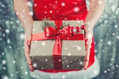 Female hands holding Christmas gift box with red ribbon, branch of fir tree on shiny xmas background. Holiday gift and decoration. Toning Royalty Free Stock Photos
