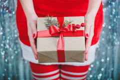 Female hands holding Christmas gift box with red ribbon, branch of fir tree on shiny xmas background. Holiday gift and decoration Royalty Free Stock Photos