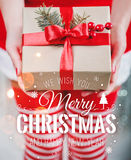 Female hands holding Christmas gift box with red ribbon and Merry Christmas and New Year typographical on shiny xmas background. Holiday gift and decoration stock photos