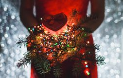 Female hands holding Christmas gift, branch of fir tree and Multicolored light decorations, on dark holiday background.  Stock Photography