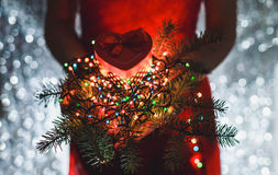 Female hands holding Christmas gift, branch of fir tree and Multicolored light decorations, on dark holiday background Royalty Free Stock Images