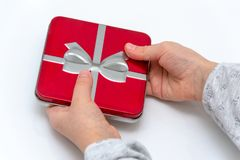 Female hands holding christmas or valentines day gift. Isolated on white background. Top view stock image