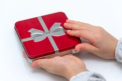 Female hands holding christmas or valentines day gift. Isolated on white background. Top view royalty free stock photos