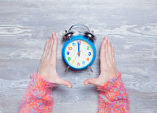 Female hands holding clock Stock Photo