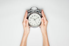 Female hands holding clock on white paper. Royalty Free Stock Photos