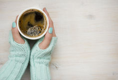 Female hands holding a coffee mug in knitted mittens Royalty Free Stock Image