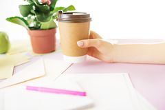The female hands holding coffee on trendy pink desk. Female hands holding coffee. Side view on trendy color pink desk. Woman and stilish workplace. Cup of Royalty Free Stock Photos