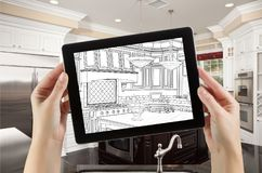 Female Hands Holding Computer Tablet with Drawing on Screen. Of Kitchen Behind stock image