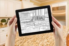 Female Hands Holding Computer Tablet with Drawing on Screen of Kitchen. Behind stock photo