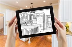 Female Hands Holding Computer Tablet with Drawing on Screen of Kitchen. Behind royalty free stock photo
